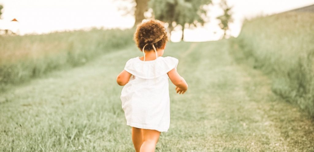 toddler running in grass